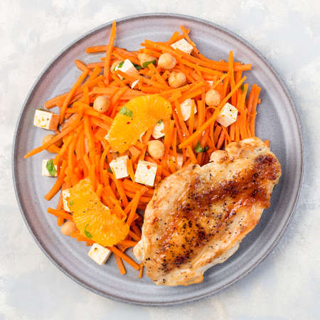 Healthy meal, roasted chicken breast with carrot, chickpeas, feta cheese salad, top view, square format, closeup 免版税图像
