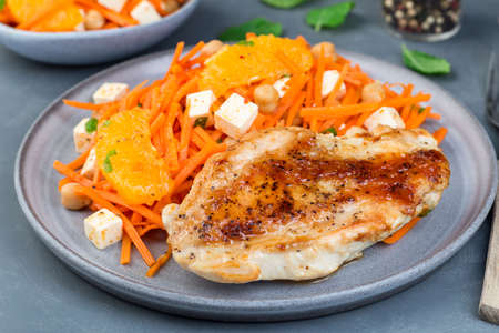 Roasted chicken breast with carrot, chickpeas, feta cheese salad, on a gray plate, horizontal
