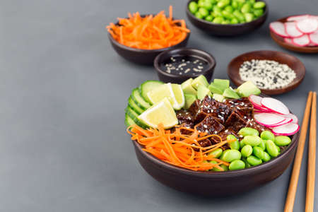 Vegetarian tofu poke bowl with brown basmati rice and vegetables, horizontal,  copy space