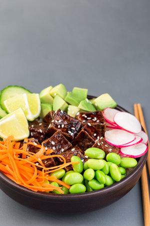 Tofu poke bowl with brown basmati rice and vegetables, vertical,  copy space