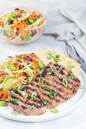 Grilled beef steak with asian style broccoli slaw salad and grilled tofu,  vertical