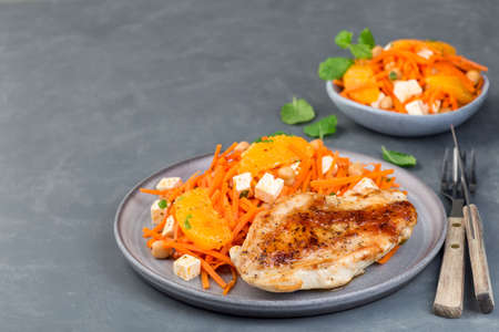 Healthy meal, roasted chicken breast with carrot, chickpeas, feta cheese salad, horizontal,  copy space