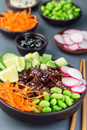 Tofu poke bowl with brown basmati rice and vegetables,  vertical
