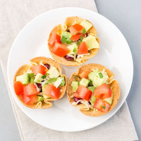 Taco cups with corn tortilla, black beans, tomatoes, avocado and cheese, on a white plate, top view, square format, closeup 免版税图像