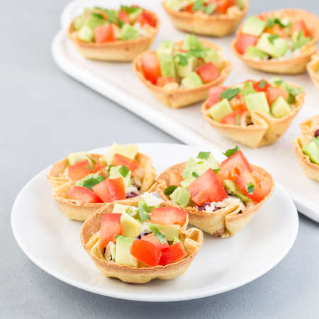 Veggie taco cups with corn tortilla, black beans, tomatoes, avocado and cheese, on a white plate, square format 免版税图像