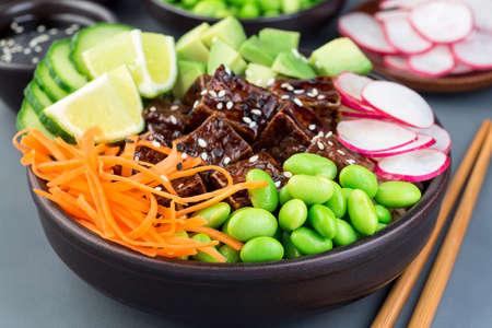 Tofu poke bowl with brown basmati rice and vegetables, horizontal, closeup 免版税图像