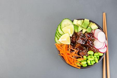 Tofu poke bowl with brown basmati rice and vegetables, horizontal, top view,  copy space 免版税图像
