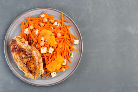 Roasted chicken breast with carrot, chickpeas, feta cheese salad, on a gray plate, horizontal, top view, copy space