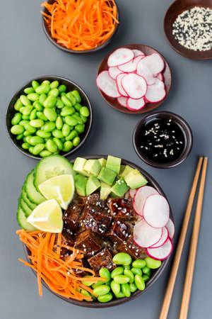 Tofu poke bowl with brown basmati rice and vegetables, vertical,  top view