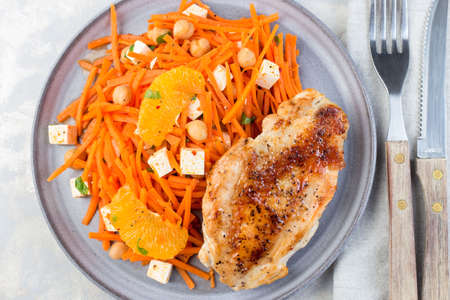 Healthy meal, roasted chicken breast with carrot, chickpeas, feta cheese salad, horizontal, top view,  closeup 免版税图像