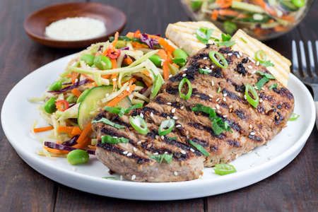 Grilled beef steak with asian style broccoli slaw salad and grilled tofu, on a wooden background, horizontal