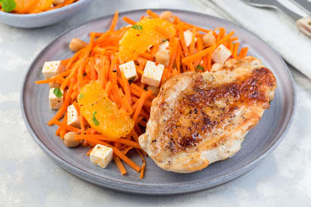 Healthy meal, roasted chicken breast with carrot, chickpeas, feta cheese salad, on a gray plate, horizontal