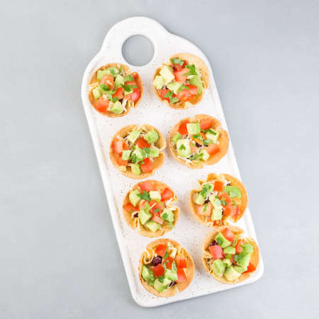 Taco cups with corn tortilla, black beans, tomatoes, avocado and cheese, top view, square format