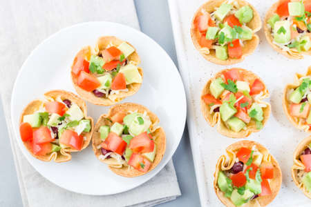 Taco cups with corn tortilla, black beans, tomatoes, avocado and cheese, on a white plate, horizontal, top view