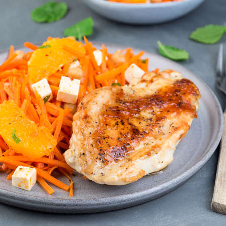 Healthy meal, roasted chicken breast with carrot, chickpeas, feta cheese salad, square format, closeup 免版税图像