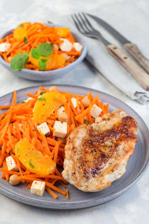 Healthy meal, roasted chicken breast with carrot, chickpeas, feta cheese salad, on a gray plate, vertical