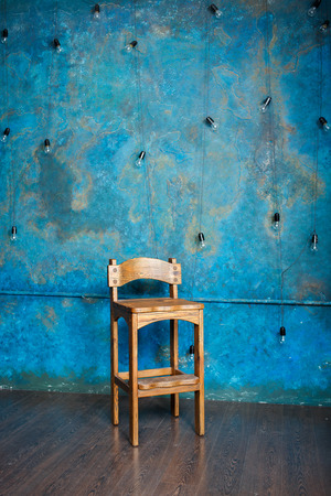 grunge room: Old wooden chair in grunge room with blue wall. Vertical Stock Photo
