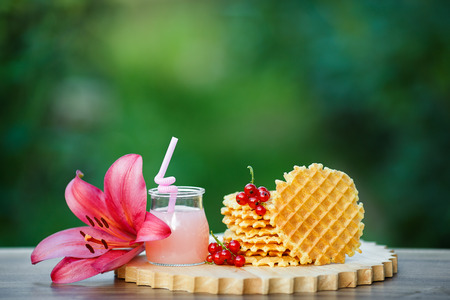grapefruit juice: Belgian waffles with fresh berries on cutting board on background of green bokeh. grapefruit juice. pink cocktail with a straw. Stock Photo