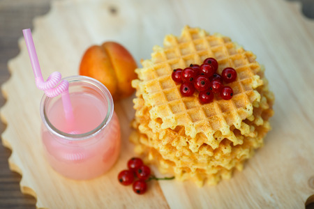 grapefruit juice: Belgian waffles with fresh berries on cutting board on background of rustic. grapefruit juice. pink cocktail with a straw.