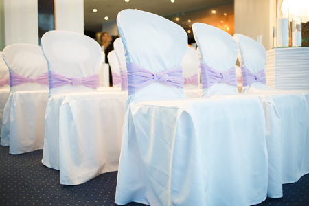 dcor: chairs decorated with white cloth with purple bows for wedding guests