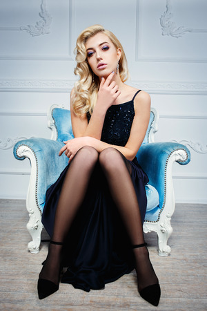 Young beautiful blond woman in dark blue dress posing at white studio on chair