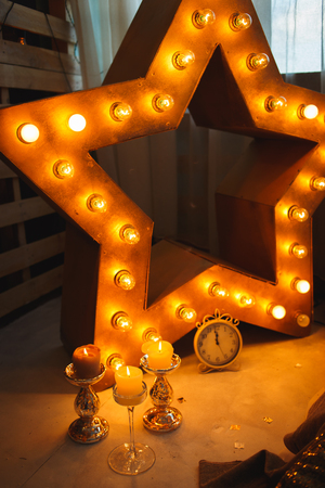 new year clock before midnight with burning candles in sconces and glowing lamps