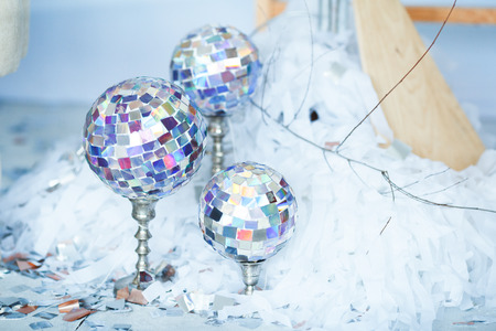 Several disco balls, mirror balls or glitter balls hanging on a stand. Daytime photo. Stock Photo