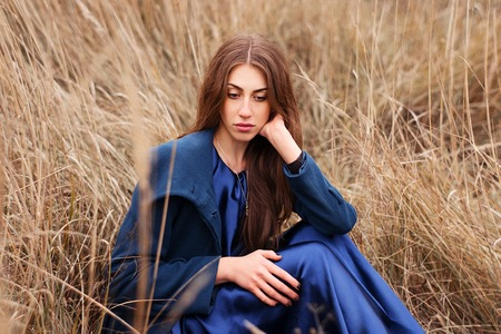 satin dress: beautiful goth girl standing in an autumn field, wearing a blue coat and a blue satin dress with a black wreath on his head Stock Photo