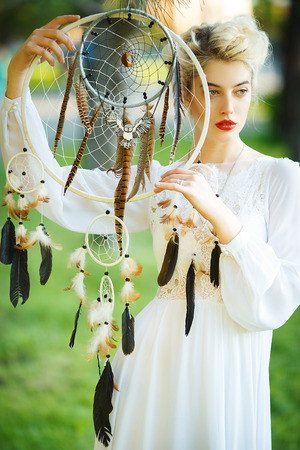Outdoor portrait of a beautiful topmodel girl with dream catcher vintage and retro tone, soft focus. Full red lips. Stock Photo