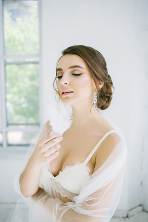 Bride with feathers in hand Stock Photo