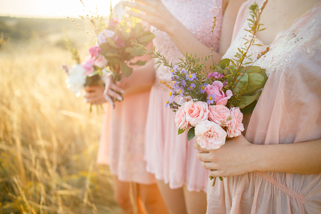 bridesmaids in pink dresses with bouquets