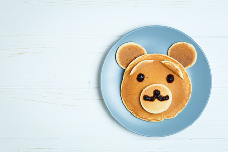 Children Bear Breakfast. Bear-shaped Pancakes - Creative Idea for Kids Easter Breakfast with Space for Text Stock Photo