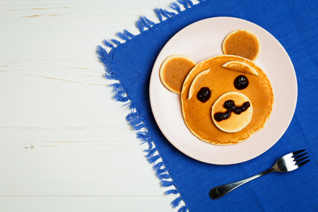 Baby pancakes in a pink plate on a blue towel with space for text Stock Photo