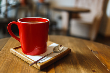 Red cup of coffee in a cafe on table. Place for rest