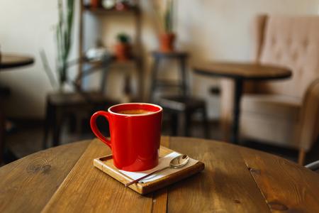 Taza de café roja en un café en la tabla. Lugar para descansar Foto de archivo