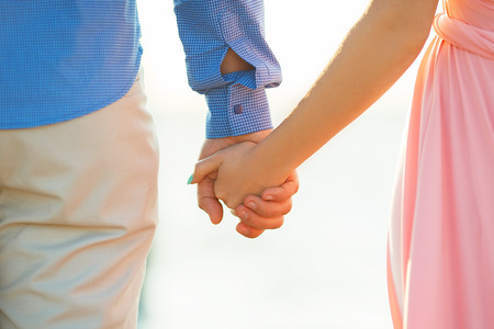 Close up of loving couple holding hands on a beach near the sea Фото со стока