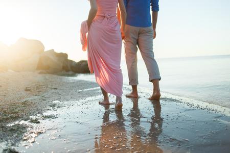Jambes sur la plage. Foot spa. Un jeune couple amoureux qui se cache et embrasse sur la plage au coucher du soleil. Deux amants, homme et femme pieds nus près de l'eau. Été amoureux