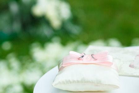 golden wedding rings on white ring bearer pillow Фото со стока