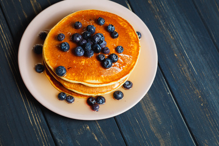 Tasty pancakes with blueberries and honey on table Archivio Fotografico