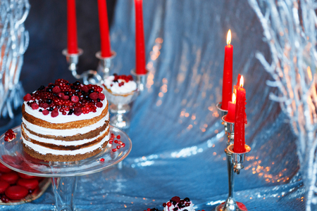 Sweet bar with muffins cakes, sweets, fruits and candle holders in area of wedding party on a silver background.