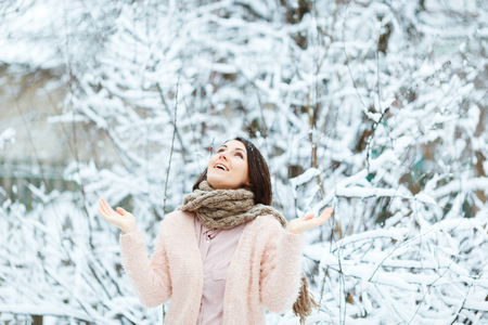 cute girl plays with falling snow in the winter forest