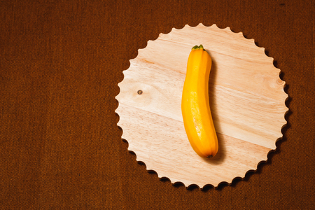 Raw yellow vegetable marrow on brown textile background. Healthy raw food, top view, flat lay.