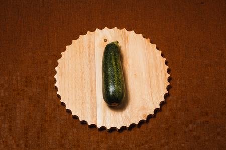 Raw green vegetable marrow on brown textile background. Healthy raw food, top view, flat lay. 免版税图像