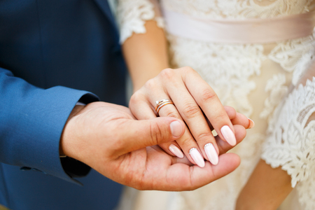 Hands of the lovers of the bride and groom. Wedding rings Banco de Imagens
