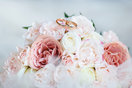 wedding golden rings with pastel pink rose