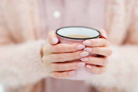 Pink cup of coffee in the hands of a cute girl who freezes in the winter forest. Stylish stock mock up