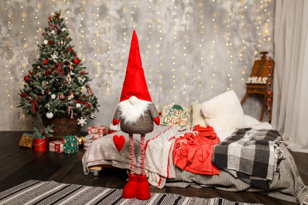 Cute winter gnome is waiting for christmas near the Christmas tree at home. Christmas time is near.