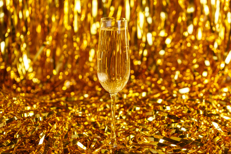 Glass of champagne with golden confetti, glitter and serpentine. Night of celebration concept Stockfoto