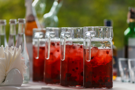 Refreshing drink with cranberries on the table, ice and rosemary, selective focus, copy space. Decanters with cranberry lemonade. Reklamní fotografie