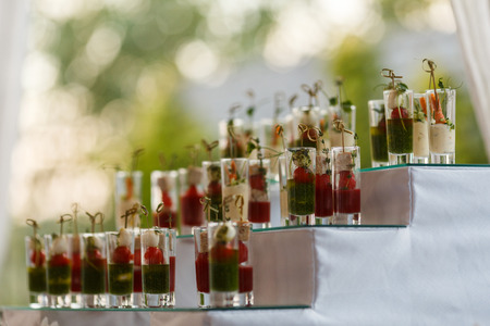 Appetizers with mozzarella and tomato in cocktail cups - selective focus